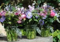 like the flowers and the colours and the containers (without the lids).  This is I think the kind of thing we'd be looking for on the tables with some smaller arrangements around them - do you think this might work?