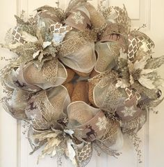 This glittery, eye catching Holiday Wreath is absolutely stunning! It would add a lot of sparkle to your Christmas or Winter Holiday decor. This creation began with a two-tone cream & white poly mesh and a natural faux burlap mesh. Three different ribbons accent the entire wreath. The ribbons include: a natural and ivory lattice print, a faux burlap with brown glitter reindeer and ivory snowflakes, and a gorgeous glitter rose gold web-like ribbon. Three large ivory and gold glitter…