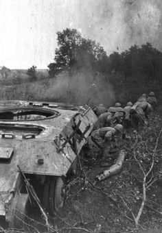 Soviet soldiers take cover with destroyed German tanks in Kursk, 280 miles southwest of Moscow.