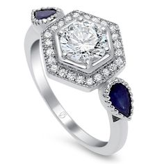 This stunning signature ring is from our Shyla collection and contains .15 carats of diamonds and .32 carats of sapphires. Hexagon pave halo is trimmed in milgrain and pear shaped blue sapphire sides complete the art deco style look.