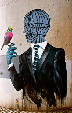 Bird on hand, cage in head - street art, bristol.