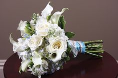 Sets crystal-centered white roses, mini callas and stock amid light blue hydrangea to proclaim that dreams come true. Variegated Italian pittosporum offers cream shading on a rich green border of backdrop greenery. Blue wrapping anchors stems with white ribbon ties. Mexico Road Florist.   stlouisbestbridal.com