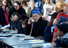People use phones supplied by FEMA on Friday in a parking lot to begin the process of getting disaster relief as the city tries to recover from the after effects of Hurricane Sandy in the Coney Island neighborhood of Brooklyn, New York