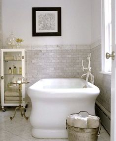 Stately Cottage Bathtub  This stately, period-style bathtub commands attention. It also demands support. If you are considering such a large tub, be sure your floors can handle the weight. The small subway tiles covering the lower half of the wall are a good design solution for the tall, narrow room.