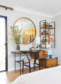 round mirror, simple furniture, fresh flowers