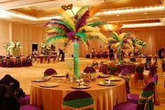 Tall feather centerpieces in a cylinder vase with green gel. All decor in Purple, Green and Gold.