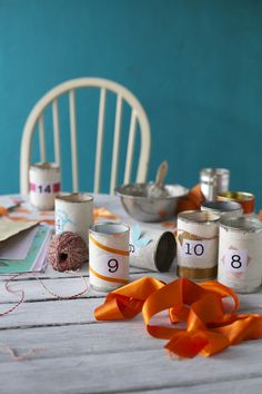 Upcycle old cans and decorate with paper and ribbon scraps to make a simple advent calendar. For more inspiration go to www.good.net.nz  Photography: Sarah Heeringa for Good magazine Cool Magazine, Handmade Crafts, Crafts To Make, Advent Calendar, Upcycle, Christmas Crafts, Ribbon, Treats, Homemade