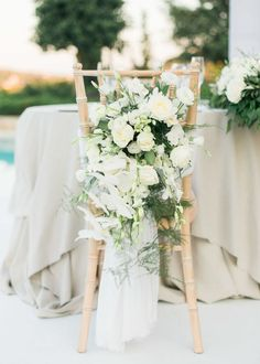 Rose and greenery floral chair embellishment: http://www.stylemepretty.com/destination-weddings/2017/02/28/a-greek-wedding-weekend-with-a-private-beach-spectacular-views/ Photography: Adrian Wood - http://www.adrianwoodphotography.com/