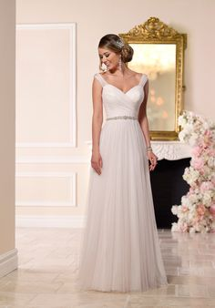 You'll find designer details on every inch of this elegant French tulle wedding dress from Stella York. Starting from the top, sparkling Diamantes are hand-sewn into the ruched tulle shoulder straps and around the figure-flattering waist belt. The bodice is essentially a gorgeous swath of ruched tulle. The back features sheer tulle detailing, a sweep train and an easy-close zipper hidden under sparkling crystal buttons.  The Knot provides price estimates to give you a general idea of the…