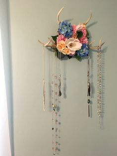 A simple and fun idea to turn antlers into jewelry hangers. Very easy to make and lights up the room. All you need is a board, antlers, and fake flora.