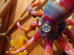 Handmade Glass Art sculpture featuring an Octopus. The Octopus features glass Millie eyes by artist Dave Strobel. The eyes are crabs with stars surrounding them.  The octopus is one of my favorite colors serendipity. The octopus and various plant life are surrounded by a 3d glass box that is versatile to be a wall hanger or allow it to set on a shelf or desk.  This glass sculpture measures 11 1/4 tall. It is just under 7 1/2 wide. The 3d glass box is 2 tall with the octopus popping out…