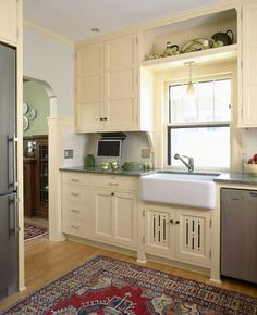 "Not all Revival kitchens are done in natural-finish hardwoods. This is a new interpretation of the ""sanitary"" white kitchen of the Note the ""Prairie feet"" and the vented undersink door with decorative cut-outs. Design by David Heide. Bungalow Kitchen, Craftsman Kitchen, Farmhouse Kitchen Cabinets, Kitchen Redo, New Kitchen, French Kitchen, Craftsman Homes, Kitchen Ideas, Vintage Kitchen Cabinets"
