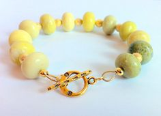 Green Yellow Stone Bracelet Green Gemstone by ClearWaterDesignsbyK, $42.67 Https://clearwaterdesignsbyk.etsy.com Https://clearwaterdesigns.info This is a Natural Stone Bracelet of Green/Yellow Peridot that graduates down from the darkest Green Bead to the lightest Yellow one.   I've used Gold Stardust beads as accents. I generally find bracelets difficult to get on & off by myself so I've used a Tibetan Silver(Gold Colour) Toggle Clasp to make this bracelet easy.