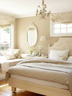 A bright and sunny bedroom decorated in neutral tones, with subtle luxurious touches such as a damask headboard and matching window treatments