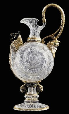 *Viennese Silver-Gilt, Enamel & Rock Crystal Ewer by Herman Ratzersdorfer, c.1880  - Surmounted by an over-hanging rim, flanked to the side by a scroll handle with a bearded-mask lower terminal, the snail-shaped body decorated with scrolling foliage, above a waisted stem, flanked to each side by a satyr head, above an oval spreading base. 12¼ in. (31 cm.) high #rock_crystal #quartz #decorative_arts #Venice