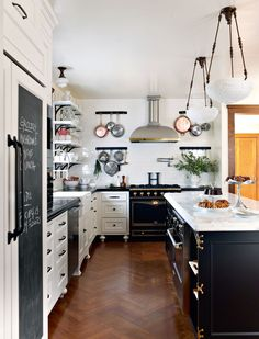 black & white kitchen. bronze accents. I like the chalk on the front of the pantry
