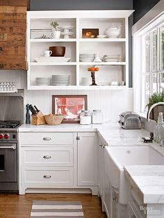 Remove upper cabinet doors to give a narrow kitchen a sense of openness. Then set off the revealed shelves with a decorative treatment. To do so, remove cabinet doors and fill in holes with wood filler. Sand until smooth, and paint or stain as desired. Apply your desired treatment to the inside after priming the interior walls./