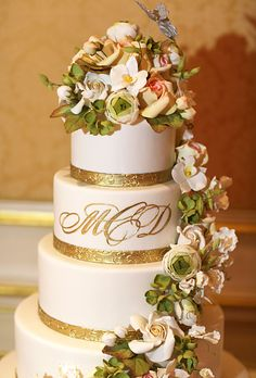 Brides.com: A Glamorous Summer Wedding in New York City. Their cake—a five-tier white dessert decorated with confectionery flowers and greens—featured the couple's married-name initials in gold script.
