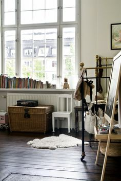 books on the window sill, brass bed, little easel, big windows xoxo