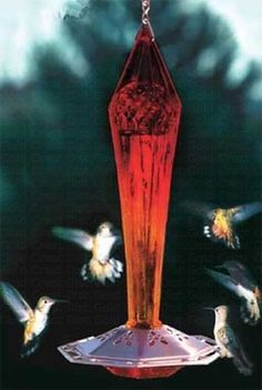 Glass Hummingbird Feeder features basin design with unique feeding ports. Multi-facet cut glass sides reflect sunlight, glows and reflects through floral pattern copper base. Eight open ports on base