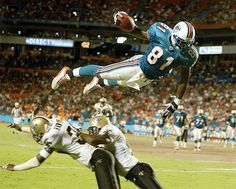 <p>Dolphins tight end Randy McMichael soars over Saints defenders Michael Hawthorne (left) and Mel Mitchell to score a touchdown during a preseason game. The rookie tight end started all 16 games and caught 39 passes for 485 yards and four TDs during the season.</p>
