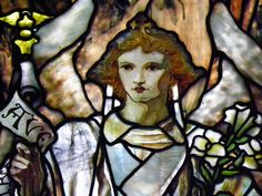 """Tiffany Nave Windows; Trinity Episcopal Church; 389 Delaware Avenue, Buffalo, NY; designed by Frederick Wilson for Tiffany Glass Company; All the folds in this drapery glass are three-dimensional. Style: Opalescent; Archangels Raphael and Gabriel; installation: 1897. Gabriel,  appears as God's messenger in both the Old and New Testaments. He carries a winged scepter, lilies and a banner with the Latin words of the annunciation """"Ave Maria."""""""