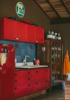 Cozinha repleta de charme: ladrilhos hidráulicos, armários pintados de vermelho e raladores que viraram luminárias.