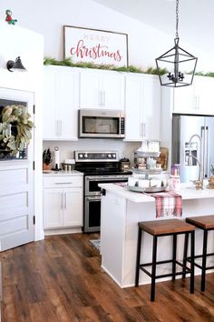 White Christmas Kitchen + Home Tour - Farmhouse Christmas Decor - White Kitchen - Magnolia Wreath - Decorating Tips for a Simple Christmas Kitchen - Christmas Sign Over Kitchen Cabinets Above Cabinet Decor, Decorating Above Kitchen Cabinets, Kitchen Decor Themes, Home Decor, Farmhouse Christmas Kitchen, Farmhouse Kitchen Decor, Diy Kitchen, Christmas Kitchen Decorations, Kitchen White