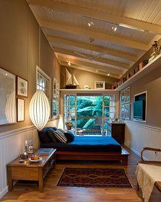 O amplo pé-direito e o telhado de uma água permitiram deixar o visual do quarto limpo. A prateleira suspensa de madeira pintada abriga objet...