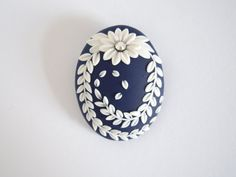 This is a nice brooch. This is made by myself. The cameo colour is ultramarine blue. I have embroidered with white polymer clay. The flower has a