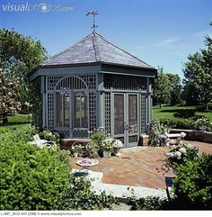 Gazebos: Brick patio outside octagon shaped dark green gazebo.  Screened in.  Lots of potted flowers and patio furniture.