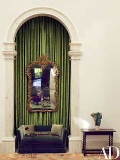 Draperies of a Fortuny cotton add warmth to a living room niche furnished with a sofa covered in a Lelièvre velour from Stark; the mirror and table are 19th-century Italian.