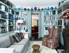 Pale blue library with cozy furniture and styled bookshelves