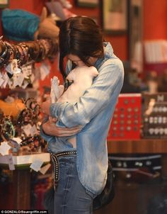 Affectionate: She bent down to kiss the top of the puppy's head while cradling it tenderly...