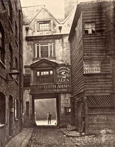 The Ghosts of Old London. At the entrance to the Oxford Arms – the Society for Photographing the Relics of Old London was set up to save the Oxford Arms, yet it failed in the endeavour, preserving only this photographic record. Victorian London, Vintage London, Old London, Victorian Street, Victorian Era, Victorian Fashion, London Pubs, Oxford London, London 1800