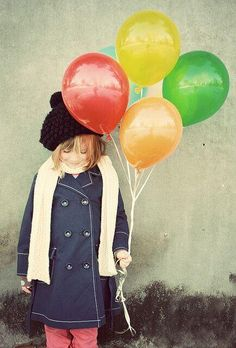 Young girl in scarf and hat holding colourful balloons
