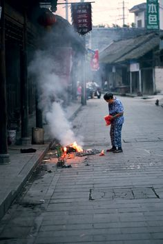 An elderly woman burning paper goblets for her deceased family members at sunset in Huaiyuan Town