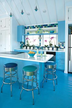 """Colorful Kitchen - Colorful Beachside Getaway - Southernliving. The bold colors also appear inside. Waves of blue drench the second-floor kitchen. A pale shade covers the walls and ceiling while a deeper shade is used on the cabinets. The wood floors carry a third shade of blue. The same hues are used in the downstairs master bedroom. Such colors are a perfect reflection of the nearby Gulf of Mexico waters.    """"When I gave the cabinetmaker the color of the cabinets, he looked at me funny…"""