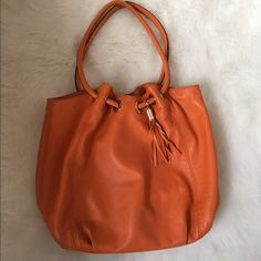 Michael Kors Tassel Handbag Leather Michael Kors handbag in orange. It has a really cute tassel on it. Perfect for everyday use! Light signs of wear on the bottom but nothing very noticeable and nothing that takes away from the integrity of the bag. No major rips or stains. 13 inches across bottom and 12 inches tall NO TRADES PLEASE Michael Kors Bags