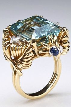 "Tiffany & Co. Jean Schlumberger Aquamarine Ring. An 18 karat gold ring, circa 1960-70, by Jean Schlumberger for Tiffany. The 14 carat aquamarine measures 16.3mm by 13.5mm by 9.4mm and is flanked by a foliate design set with two full cut diamonds, a cabochon sapphire and a cabochon emerald. Signed ""Tiffany Schlumberger 18k"" The ring fits an approximate 7.5 size finger. It comes with the original Tiffany box."