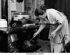 1950s HOUSEWIFE TESTING ROAST BEEF IN OVEN TO SEE IF IT IS DONE COOKING - Stock Image