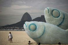 A woman looks at an installation made of recycled plastic bottles representing fishes, in Botafogo beach, in Rio de Janeiro. Photo: AFP