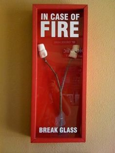 """In case of fire - Break Glass; bought a frame big enough to hold my four marshmallow sticks, made a shadowbox using pieces of wood and plywood, spray painted all wood pieces red, created a stencil that said """"in case of fire"""" and spray-painted that in white. Because my stencil was not sticking to the glass, when I spray-painted the words the spray paint ultimately spread everywhere and I had to use goof off to remove the excess white spray paint splatter."""