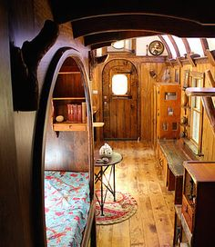 A sleeping nook with a curved opening is part of the detailed woodwork found in the Old Time Caravan. A one-of-a-kind tiny house with a curved roof, round windows, live edge maple desk, mahogany storage staircase, and intricate woodwork throughout. Tiny House Living, Small Living, Living Room, Bus Living, Tiny House Bedroom, Bedroom Small, Kitchen Living, Sleeping Nook, Bed Nook