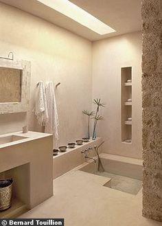Un puits de lumière inonde une autre salle de bains en tadelakt, aux formes rectilignes. Miroir artisanal encadré d'os, Mustapha Blaoui. Linge de toilette, Brigitte Perkins