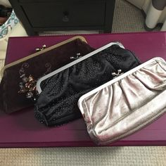 Set of Three Express Clutches Three great clutches from Express all in a different color. The light gold metallic one does have a mark on the inside (pictured) and the clasp to close it doesn't hold all that well. The other two are in perfect shape. I've never used the brown velvet one and the black one has all its beads attached with no loose ones or frays. Express Bags Clutches & Wristlets