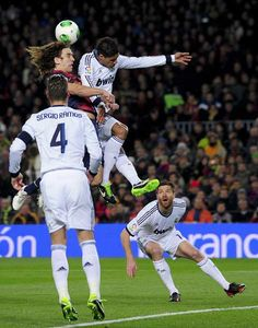 Barcelona's captain Carles Puyol (L) vies with Real Madrid's French defender Raphael Varane (R)  during the Spanish Cup semi-final second-leg football match FC Barcelona vs Real Madrid CF at the Camp Nou stadium in Barcelona on February 26, 2013.