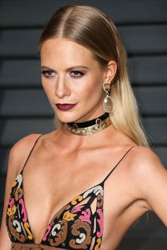 Poppy Delevingne wears an embellished choker, bold earings and a colourful strappy dress.