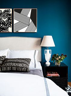 Black blue and white bedroom color scheme with bold graphic artwork.