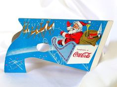 This vintage Coca Cola paper pop gun has Santa featured on both sides. On one he is driving off with his sleigh and reindeer, and on the other he is putting together a car with some children around him. The gun is about 9 inches (23 cm) long and 5.5 inches (14 cm) tall.  Condition: Excellent! One small fold mark on sleigh side; paper is intact, but split about 1/4 inch at the peak where it meets the gun.  Check here for more Christmas figurines and collectibles…